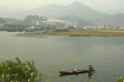 A view of Mogok, its lake (a former gem mine) and pagoda-covered mountains.