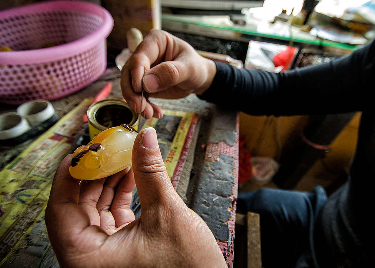 Applying a reddish varnish to the surface of a jade-like material in a workshop in Ruili's jade market. Following the treatment, which probably involves firing in an oven, the treated portions assume a reddish color that simulates the natural oxidation staining on the surface of jade boulders. Lotus Gemology on jade, nephrite, jade treatments.