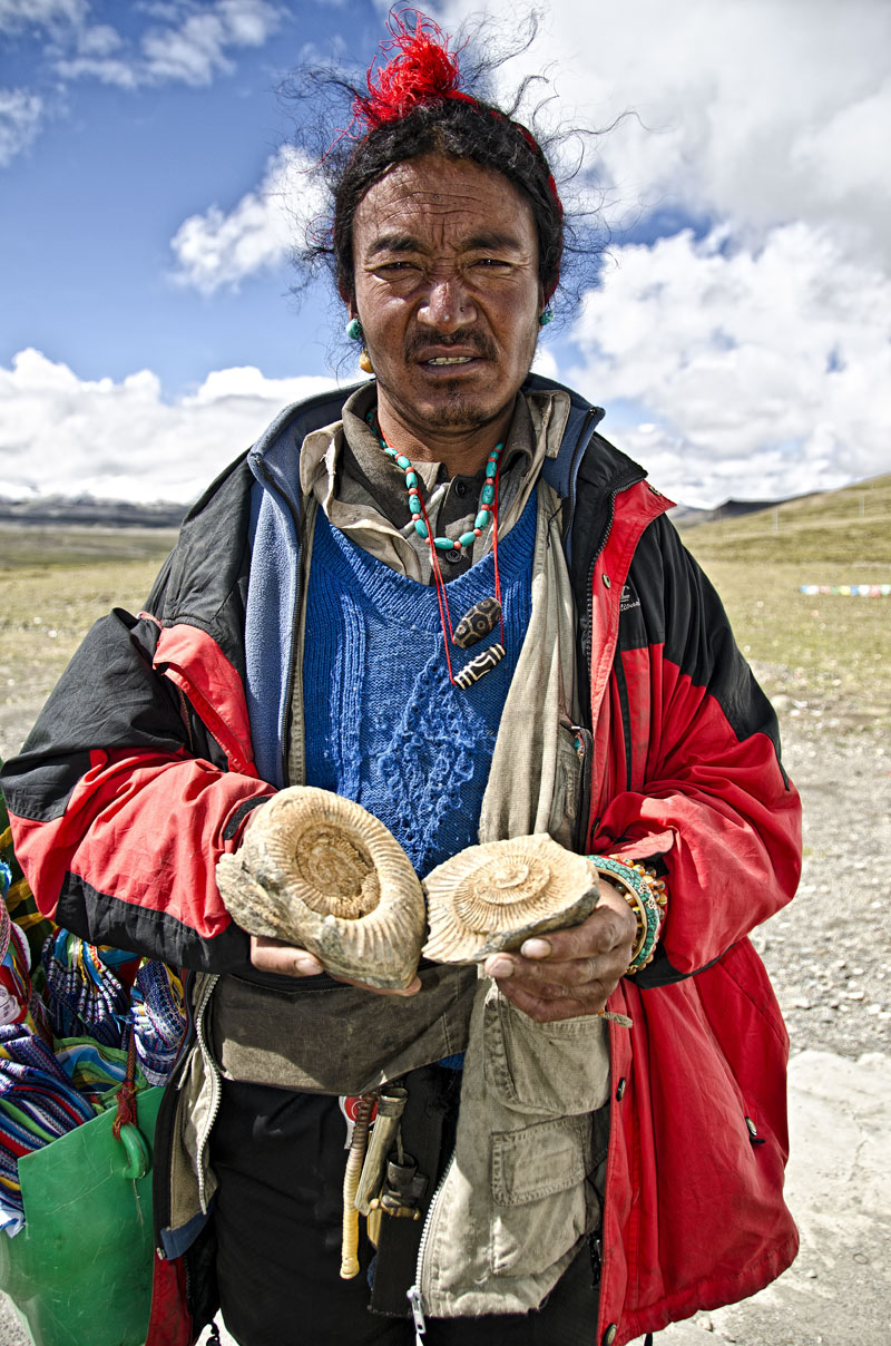 Ancient wisdom Tibetan man offering fossils for sale atop, Tropou La (4500 m; 14,763 ft). Before the collision with the Indian subcontinent, Tibet was a sea, and marine fossils are thus found throughout the land. Photo: Richard W. Hughes
