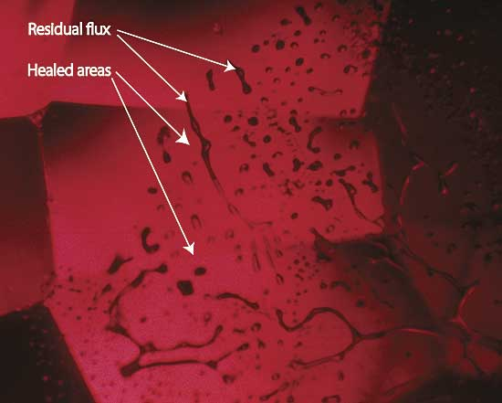 Figure 6. Flux-healed fracture Moderate magnification reveals a flux-healed fracture in a Mong Hsu ruby from Burma. The irregular dark areas are pockets of residual flux, while the red areas in between are where the once open fracture has healed shut with microscopic amounts of what is essentially synthetic ruby. In some places, the flux residue appears transparent. This is an illusion produced by reflection off the surfaces of the flux pockets. Photo: R.W. Hughes