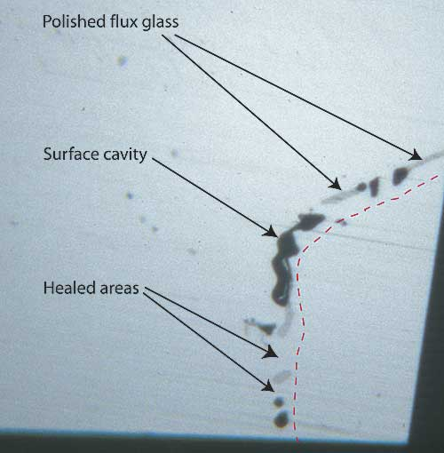 Figure 7. Surface of a flux-healed fracture A highly magnified photo showing a single facet's surface in reflected light where a fracture breaks the surface in a flux-healed Mong Hsu ruby. The dotted red line shows the path of what was once an open fracture, displaced slightly to the right so you can see surface detail. The irregular black areas are surface cavities where bubbles in the flux were cut through, while the irregular gray areas are residual flux glass that has been polished. Note the lower luster compared with the surrounding corundum. In between the surface cavities and flux glass are healed areas, indistinguishable from the surrounding corundum. Photo © R.W. Hughes
