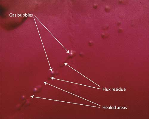 Figure 10. Flux residue may be two-phase Highly magnified photo showing flux residue within a flux-healed Mong Hsu ruby. Note that the small flux-filled pockets may contain gas bubbles formed by contraction of the flux residue as it cools. Photo: R.W. Hughes