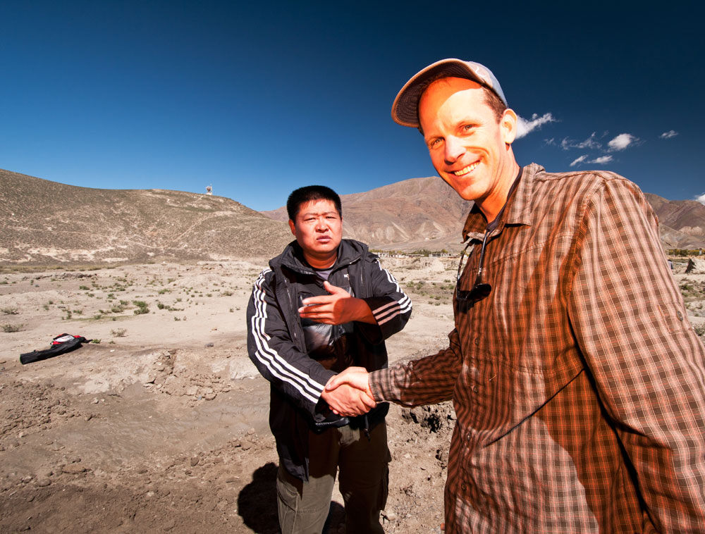 Figure 11. Liberation Day Li Tong and Brendan Laurs shortly after we found andesine beneath a randomly chosen bush. Li Tong has worked for years to show the world that Tibetan andesine is real. Photo: Richard W. Hughes