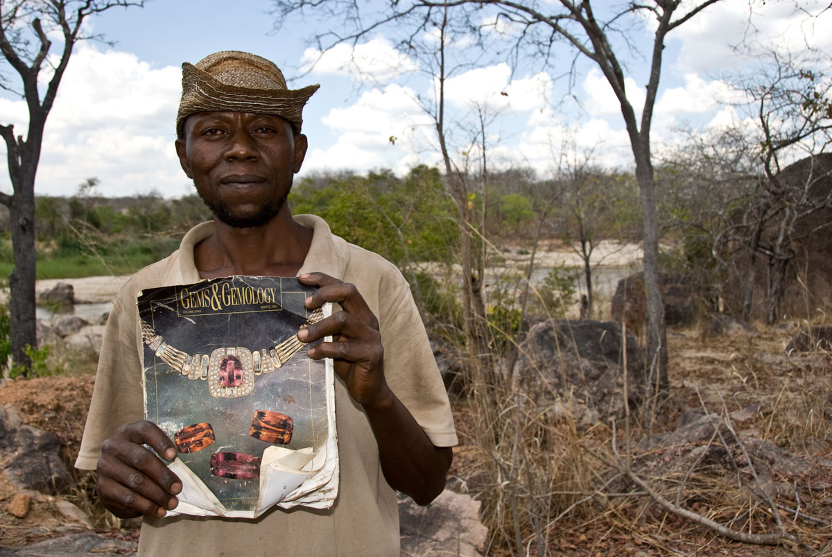 Miner Joseph Mayunga displays one of his prize posessions, a Gems & Gemology magazine that covers the gems of TanzaniaMiner Joseph Mayunga displays one of his prize possessions, a Gems & Gemology magazine that includes an article on the gems of Tanzania, given to him by a Sri Lankan dealer after a successful chrysoberyl deal. At the time of our visit in October, 2007, Joseph had been living and mining at the Muhuwesi river for more than seven years. Photo: Richard W. Hughes, Lotus Gemology.