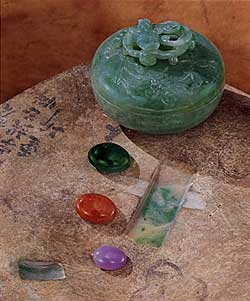 "Figure 1. ""Windows"" cut into this otherwise undistinguished boulder from the Burma Jade Tract reveal the presence of a rich green in the jadeite beneath the skin. Boulders such as this are the source of the fine green, orange-red, and lavender cabochons that are much sought-after in China and elsewhere. The bowl is approximately 6 cm wide x 5 cm high. The cabochons measure approximately 15 x 19 mm (green), 13 x 18 mm (orange-red), and 10 x 14 mm (lavender). Courtesy of Bill Larson and Pala International; photo © Harold & Erica Van Pelt."