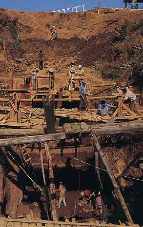 Figure 5. In some areas at Tawmaw, miners must dig deep shafts through the overburden to reach the jadeite dikes. Dirt and gravel are removed by a rudimentary winch-and-bucket system. Photo © 2000 Fred Ward.