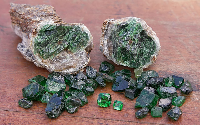 Tsavorite porphyroblast, along with rough and faceted gems from Tsavo area, Kenya. Stones courtesy: Genson Micheni Musa/ Tsavolite Co Ltd, Photo: V. Pardieu/Gübelin Gem Lab, 2007.